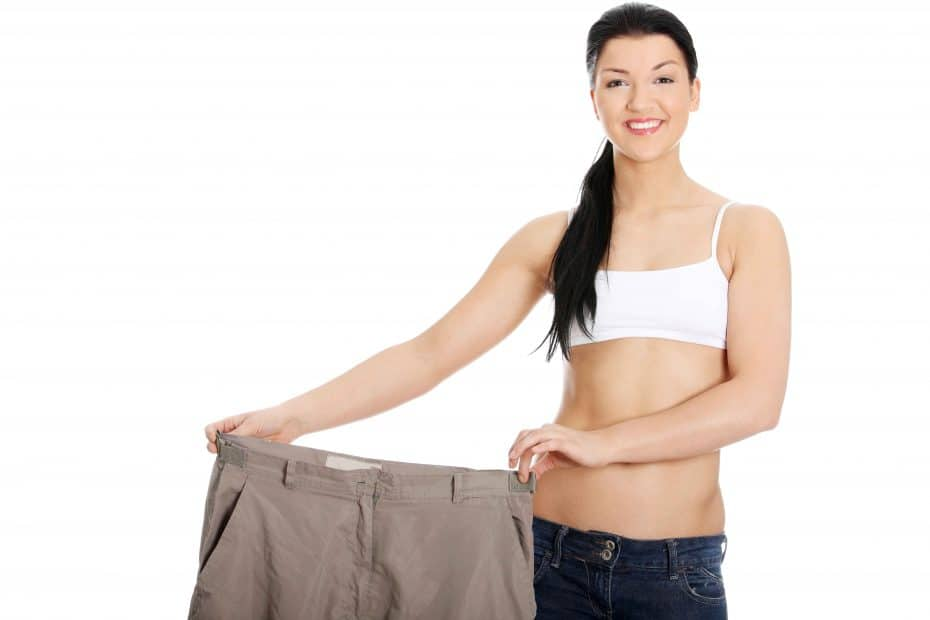 Young happy woman showing how much weight she lost